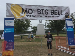 A runner ringing the big bell at the end of the race